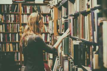 Woman searching through book stack